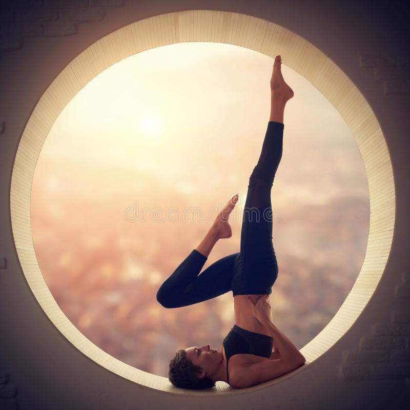 Beautiful sporty fit yogi woman practices yoga Salamba Sarvangasana - shoulderstand pose in a window. Beautiful sporty fit yogi woman practices yoga handstand stock image