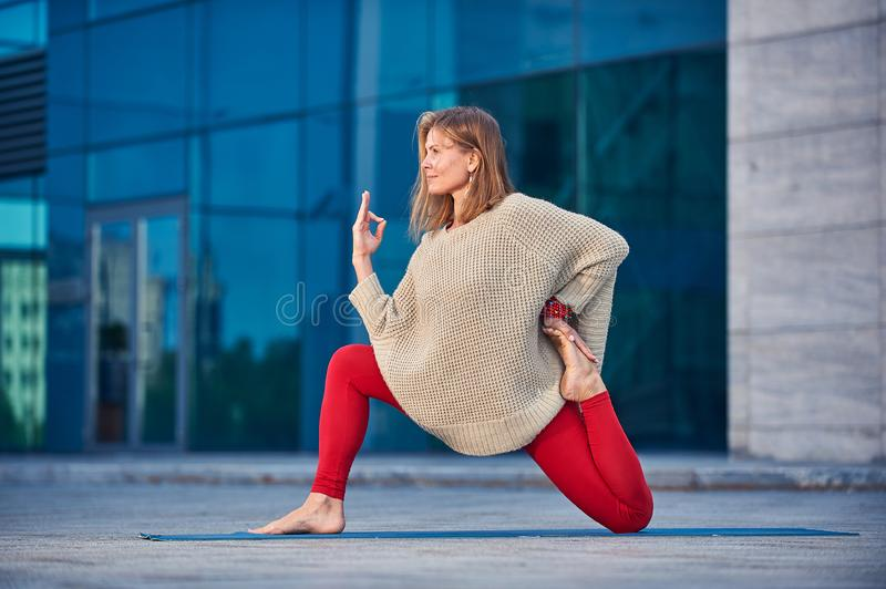 Beautiful sporty fit yogini woman practices yoga asana Ashva Sanchalasana - equestrian pose outdoors against the background of a stock photos