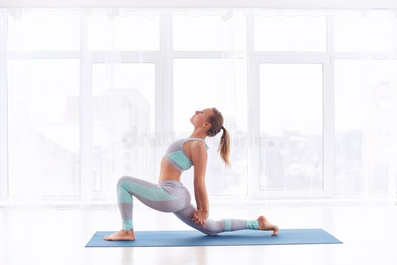 Beautiful sporty fit yogini woman practices yoga asana Ashva Sanchalasana - equestrian pose at the yoga studio. Beautiful sporty fit yogini woman practices yoga royalty free stock image
