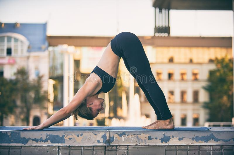 Beautiful young woman practices yoga asana downward facing dog in the city. Beautiful sporty fit yogini woman practices yoga asana downward facing dog in the stock image