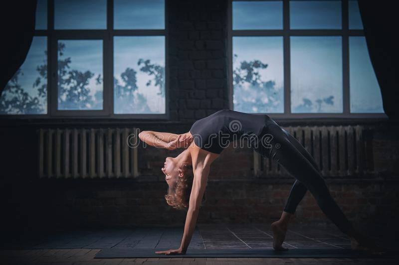Beautiful sporty fit yogini woman practices yoga asana Wild Thing Pose in the dark hall royalty free stock photos