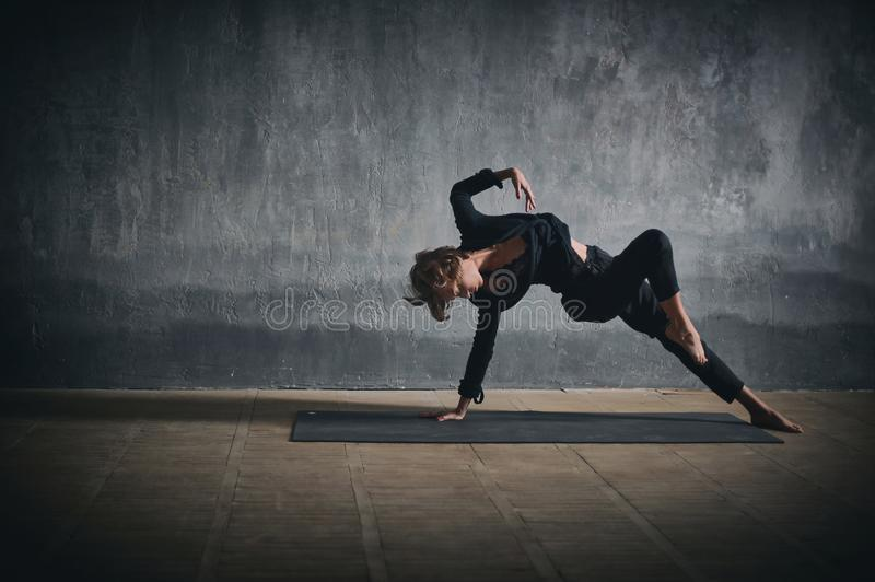 Beautiful sporty fit yogini woman practices yoga asana Wild Thing Pose in the dark hall royalty free stock images