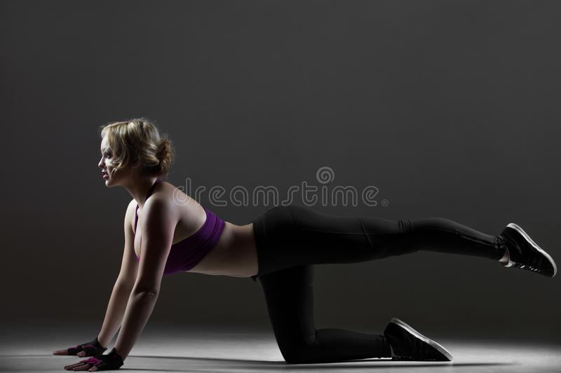 Beautiful sporty girl doing leg swings stock photography