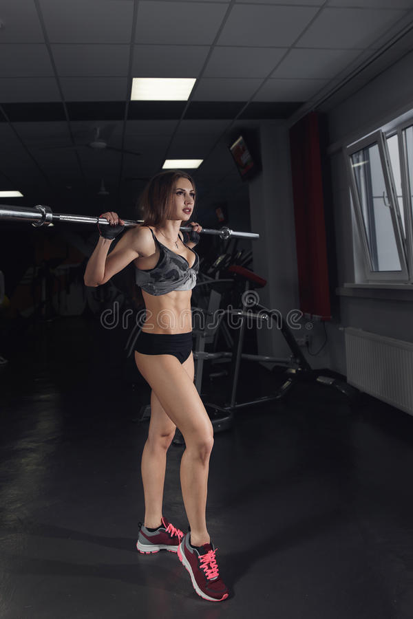 Beautiful sporty woman doing squat workout in gym. stock photo