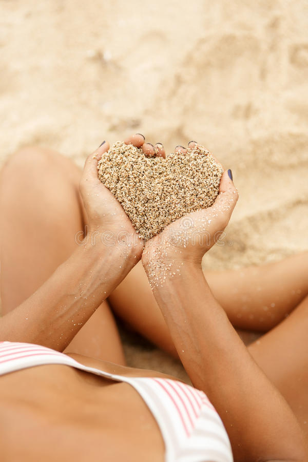 Beautiful sporty surfer girl at the beach. Hands hold sand in shape of hart above tropical beach. Beautiful fit sporty surfing girl in bikini sit at sunrise or stock images