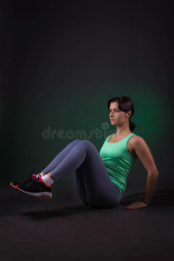 Beautiful sporty woman doing exercise on a dark background with green backlight royalty free stock photo