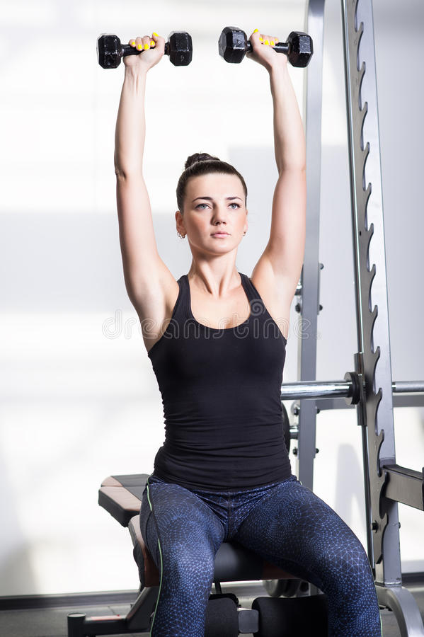 Beautiful sporty woman doing power fitness exercise at sport gym stock photos