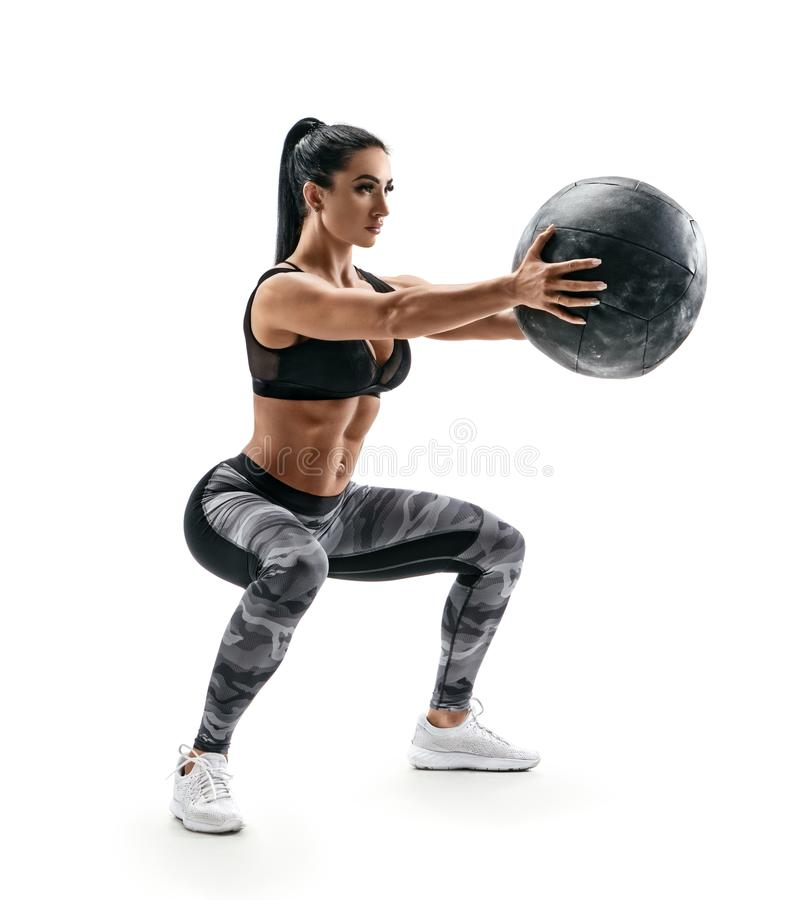 Beautiful sporty woman doing squats with med ball. stock images