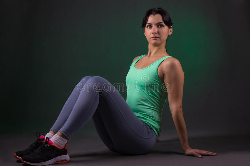 Beautiful sporty woman, fitness woman doing exercise on a dark background with green backlight royalty free stock photography