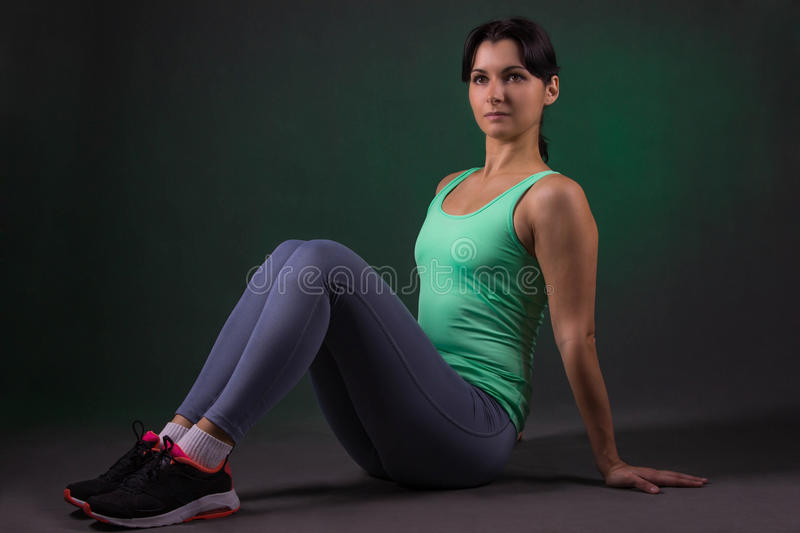 Beautiful sporty woman, fitness woman doing exercise on a dark background with green backlight stock image