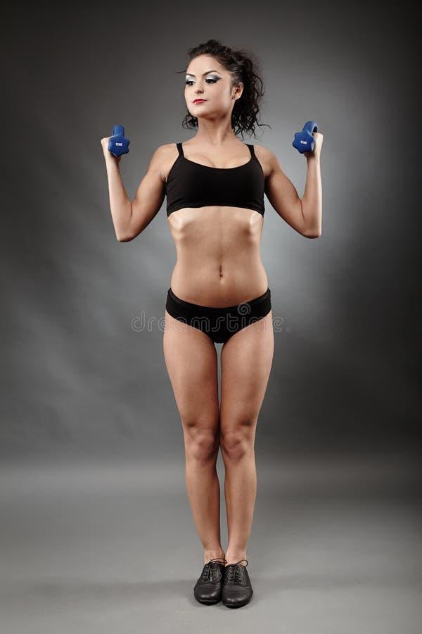 Beautiful sporty woman lifting dumbbells stock image