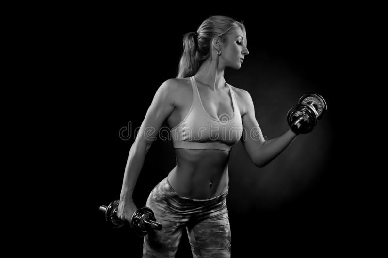 Beautiful sporty  woman working out with dumbbells royalty free stock photos