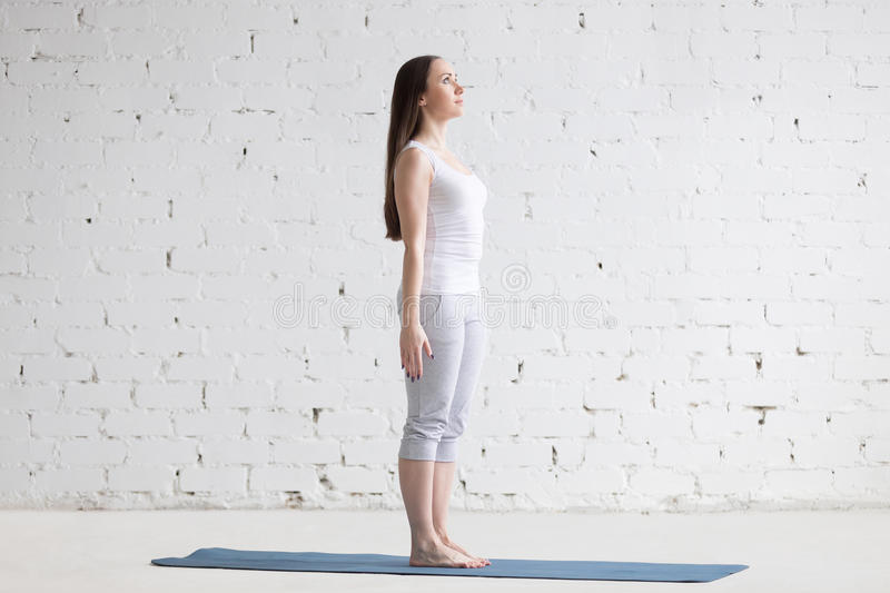 Beautiful sporty young woman doing Tadasana pose in white loft royalty free stock image