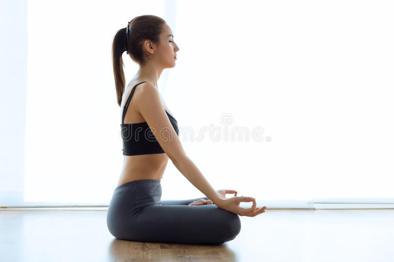 Beautiful sporty young woman doing yoga in lotus position at home. royalty free stock photos