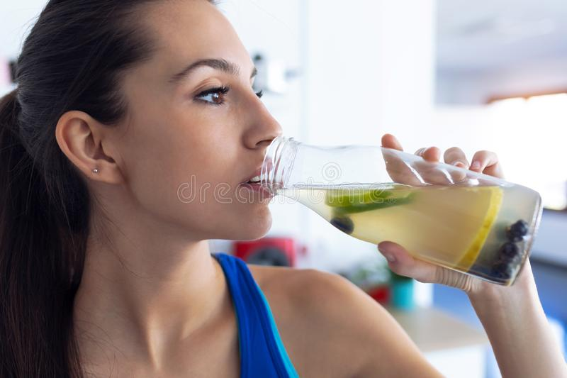Beautiful sporty young woman drinking detox juice in the kitchen at home stock photography