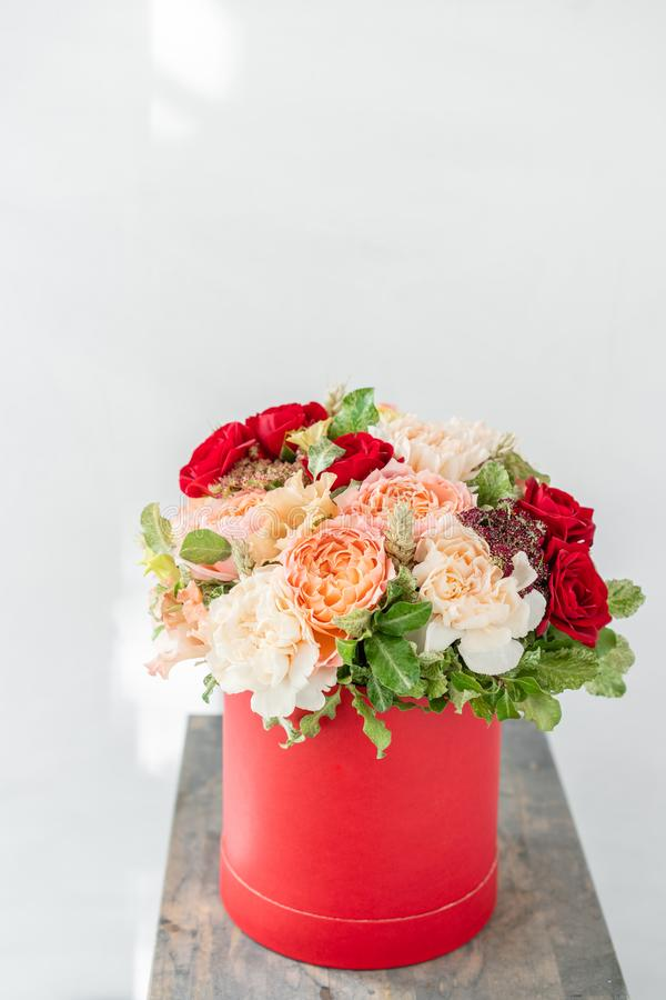 Beautiful spring bouquet in head box. Arrangement with mix flowers. The concept of a flower shop. Red color. Work stock images