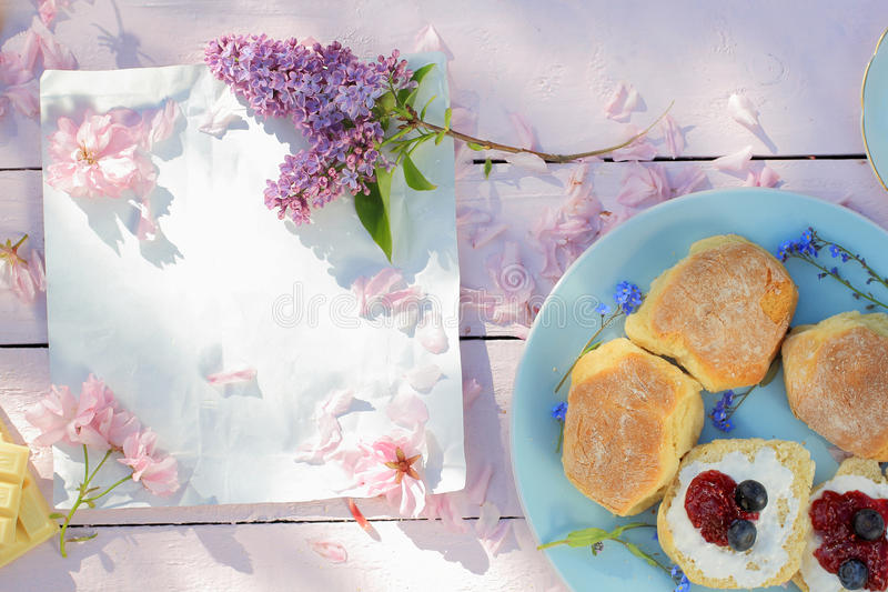 Beautiful spring breakfast background with Scottish scones, lilac and cherry flowers royalty free stock photography