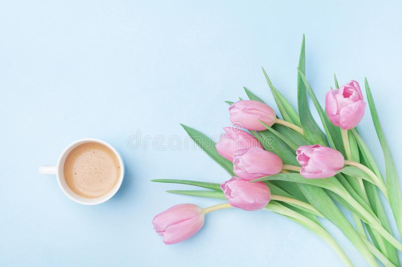 Beautiful spring breakfast on Mothers or Womans day. Bouquet of pink tulips and coffee cup on blue pastel table top view. Flat lay stock photography