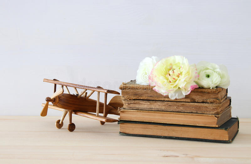 Beautiful spring flowers on the old books next to plane toy. On wooden table stock photography