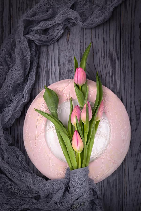 Beautiful flowers pink tulips and a pink plate on a gray background. Top view, free space stock image