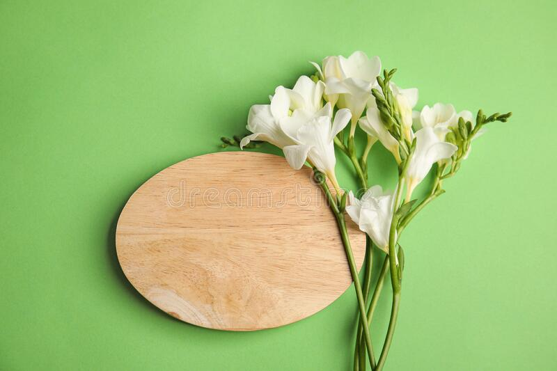 Beautiful spring freesia flowers and wooden board on background, flat lay. Space for text. Beautiful spring freesia flowers and wooden board on green background royalty free stock images