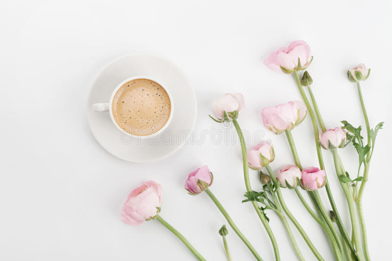 Beautiful spring Ranunculus flowers and cup of coffee on white desk from above. Greeting card. Breakfast. Pastel color. Flat lay. royalty free stock photography