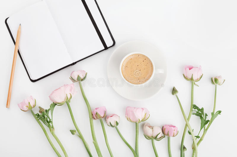Beautiful spring Ranunculus flowers, empty notebook and cup of coffee on white table from above. Greeting card. Breakfast.Flat lay. Beautiful spring Ranunculus stock photo