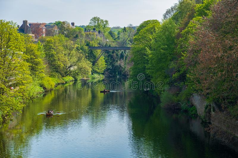 Beautiful spring scene of people rowing in boats along River Wear in Durham, United Kingdom. Durham, United Kingdom - April 30, 2019: Beautiful spring scene of stock photography