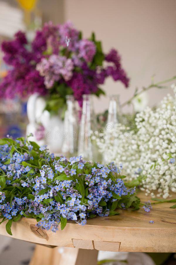Beautiful spring and summer flowers on the table ready for bouquet. Many forget-me-not, lilac blossoms royalty free stock image