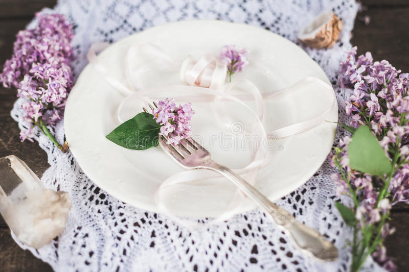 Beautiful spring table set up with boho flower decoration. Beautiful spring wedding event table set up with boho style lilac flower decoration. Top view flat stock images