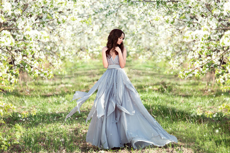 Beautiful spring walk. In the garden among the blooming trees in April a lady in a long dress pastel , creative computer colors, fashionable toning stock photos