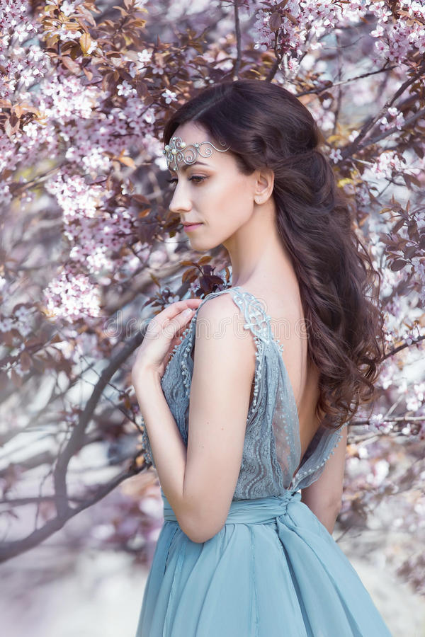 Beautiful spring walk. In the garden among the blooming trees in Aprilna lady in a long dress pastel , creative computer colors, fashionable toning stock photography