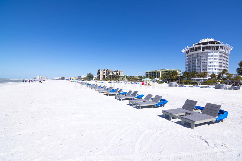 Beautiful St. Pete Beach, Florida. Resort and hotel lounge chairs lined up on clean, white sand under clear, blue sky at beautiful St. Pete Beach in St stock image