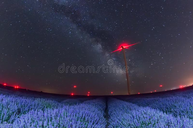 Beautiful starry night sky with milky way over a field of lavender and red lights of wind turbines stock image
