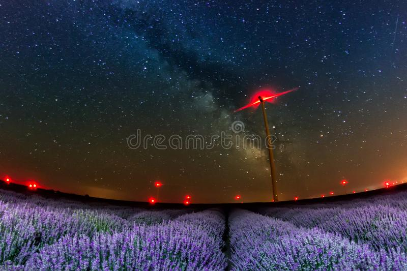 Beautiful starry night sky with milky way over a field of lavender and red lights of wind turbines stock photo
