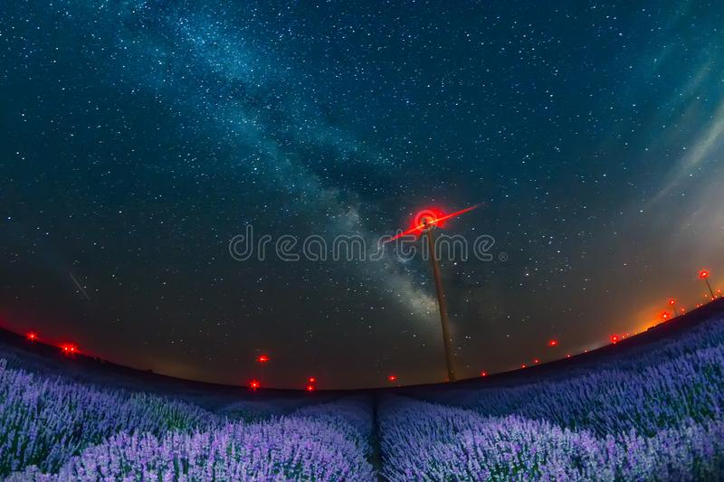 Beautiful starry night sky with milky way over a field of lavender and red lights of wind turbines royalty free stock image