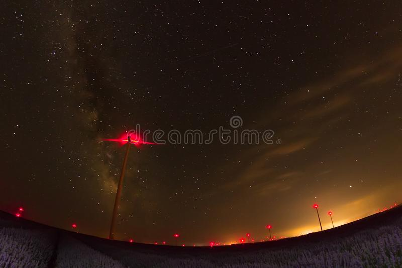 Beautiful starry night sky with milky way over a field of lavender and red lights of wind turbines stock photos