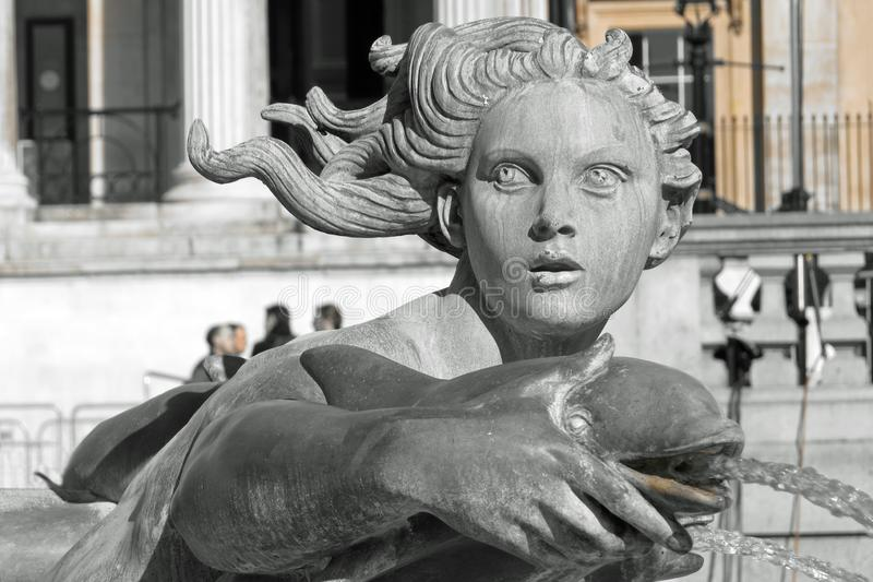 Beautiful statue of a woman and a dolphin at a water fountain, stock photography