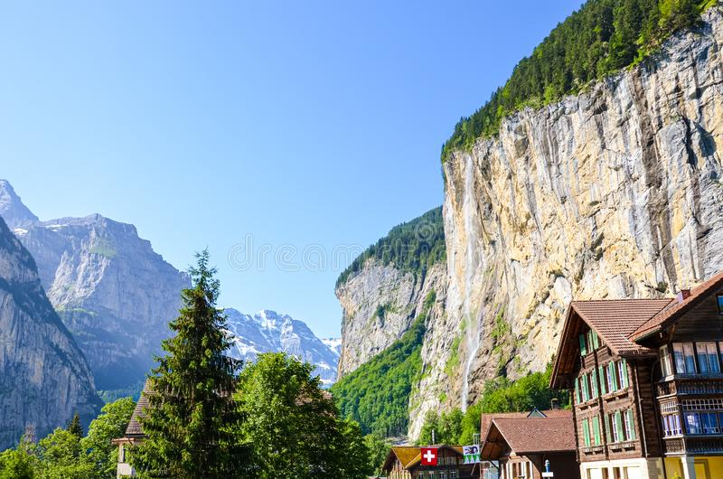 Beautiful Staubbach Falls in picturesque village Lauterbrunnen, Switzerland photographed in summer season with local chalets. Popular tourist attraction. Swiss royalty free stock photography