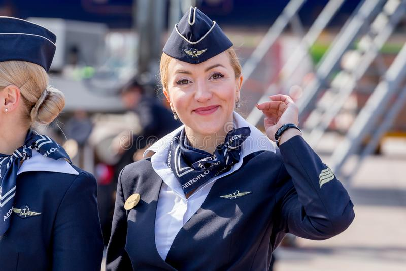 Beautiful stewardess dressed in official dark blue uniform of Aeroflot Airlines on airfield. Passenger jet aircraft on background. royalty free stock photography