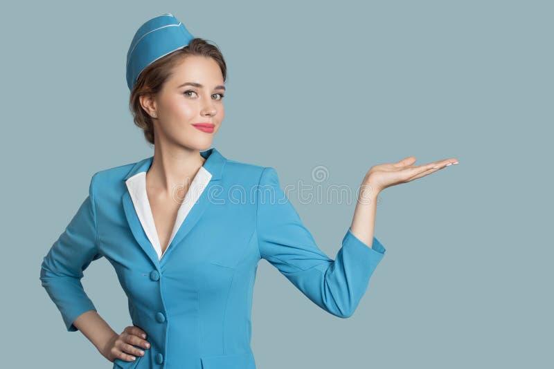 Beautiful stewardess holding blank on her hand. stock photography