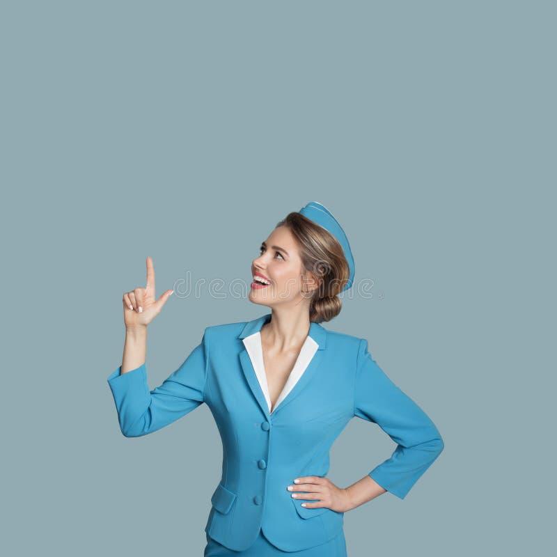 Beautiful stewardess points a finger on copyspace. stock photos