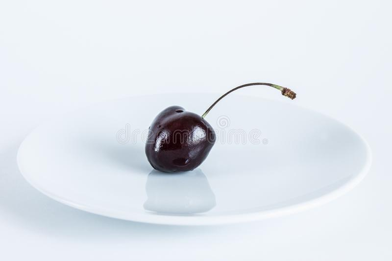 Burgundy cherry berry on a white plate close-up on a white background. Beautiful still life Burgundy cherry berry on a white plate close-up on a white background royalty free stock image