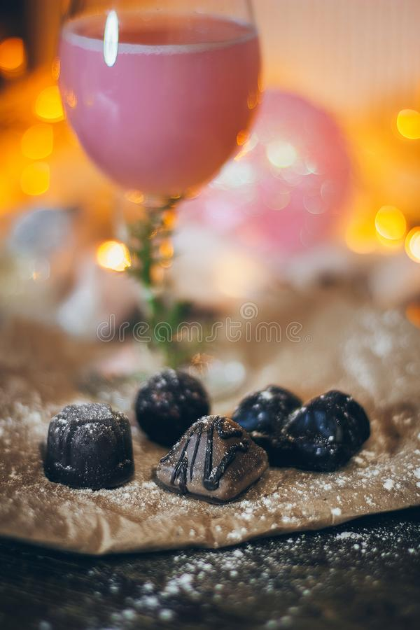 A beautiful still life scene in Christmas mood with a glass of pink beverage and sweets on the Christmas lights backgroun royalty free stock photo