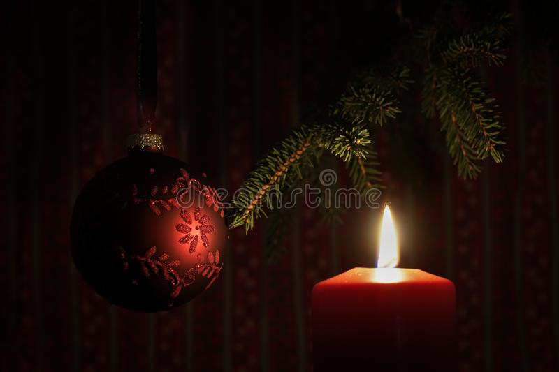 Red lit candle and Christmas tree ball stock photo