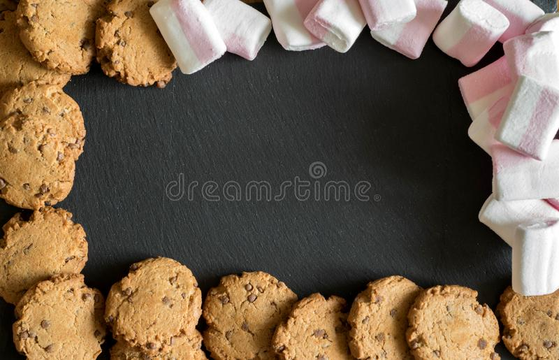 On a beautiful stone background is randomly scattered pink and white marshmallows, shortbread chocolate chip cookies with pieces o. On a beautiful stone stock image
