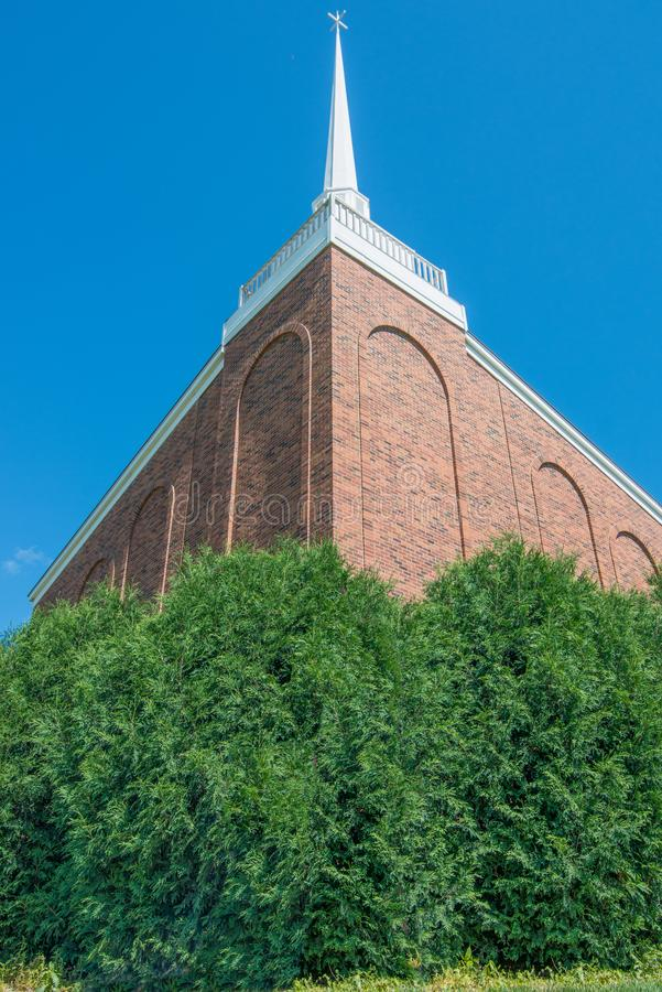 Beautiful stone church with white spire - clear vivid blue skies with lush green bushes in front - wide angle - green, brown, whit royalty free stock photo
