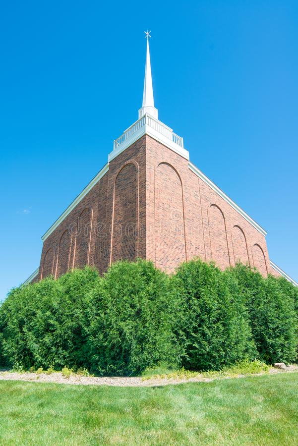 Beautiful stone church with white spire - clear vivid blue skies with lush green bushes in front - wide angle - green, brown, whit royalty free stock photography