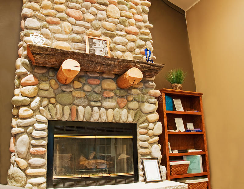 Beautiful Stone Fireplace. This beautiful tall stone fireplace is featured in a corner of an interior room for a cozy warm feeling stock images