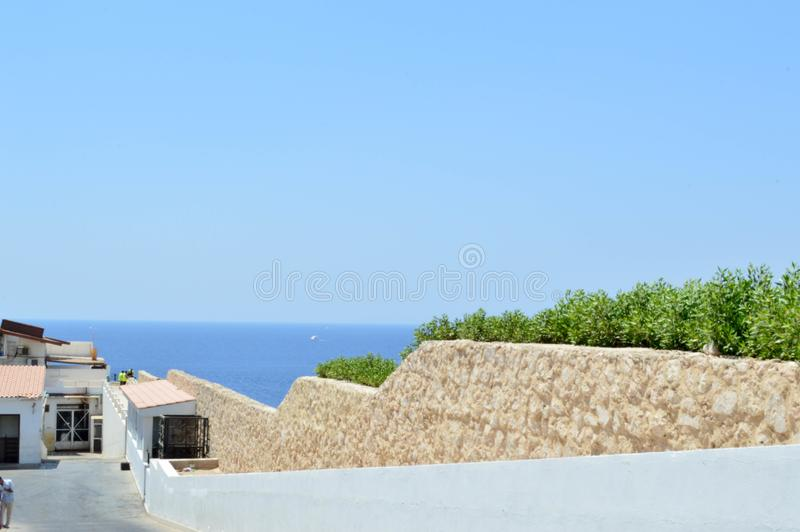 Stone wall descending down to the sea with blue water in a tropical resort and a white building with a roof of red shingles and gr stock photography